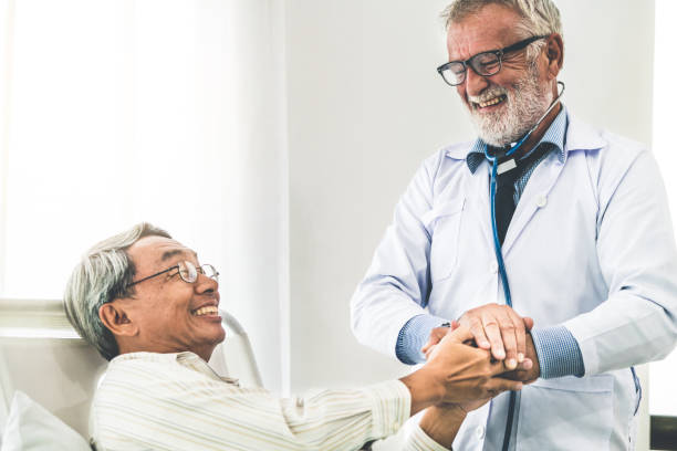 mature doctor and senior patient in hospital ward. - inpatient stock pictures, royalty-free photos & images