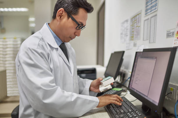 Mature doctor checking medicine on computer stock photo
