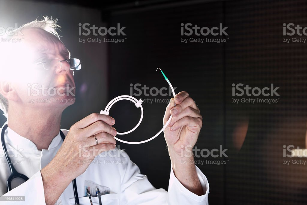Mature doctor demonstrating catheter stock photo