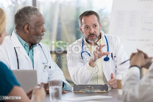A serious mature male doctor sits at a table in a board room with unrecognizable colleagues.  He looks at them as he gestures and speaks.  A senior doctor sits beside him and listens.