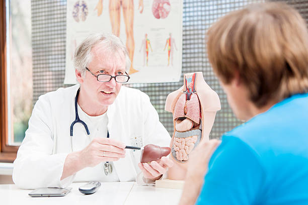Mature doctor explaining liver problems stock photo