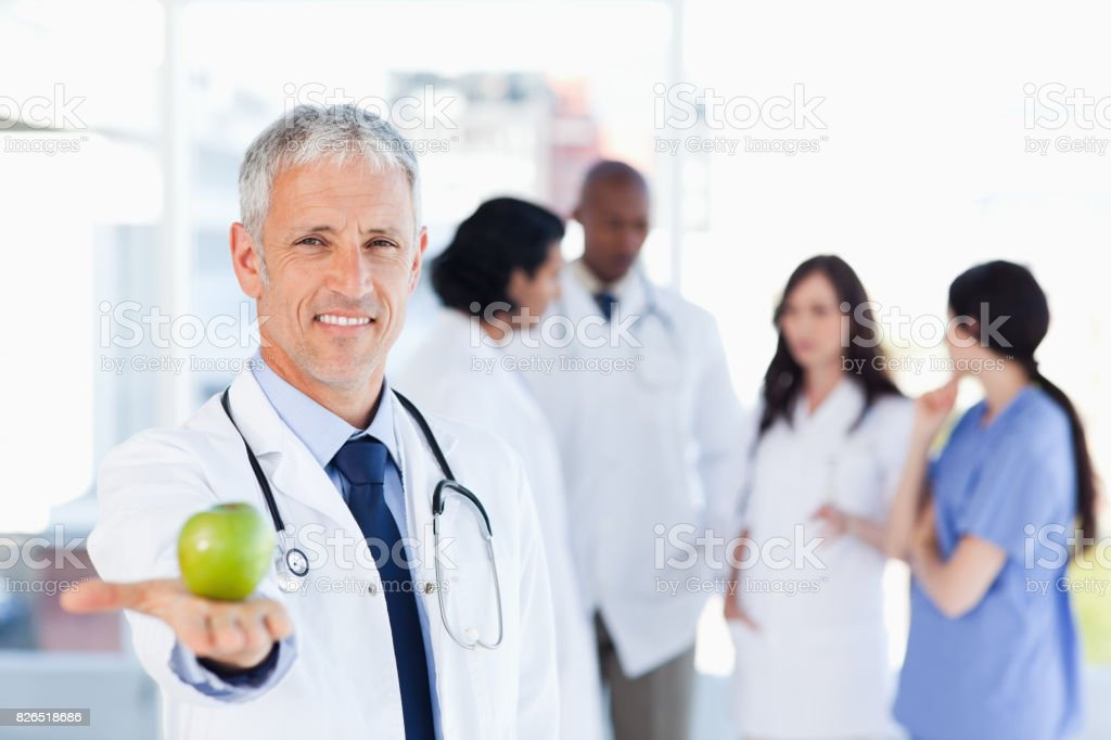 Mature doctor holding an apple in his right hand stock photo