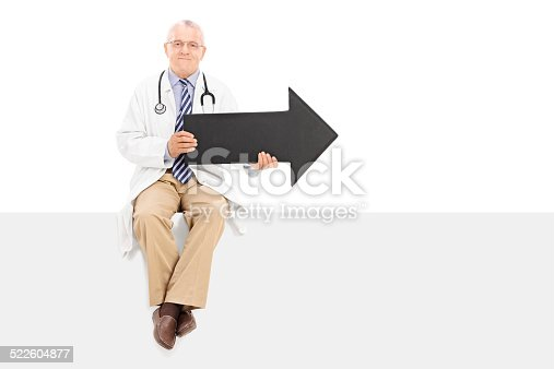 istock Mature doctor holding an arrow and sitting on a panel 522604877
