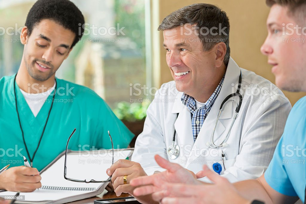 Mature doctor leading staff meeting with nurses and employees royalty-free stock photo