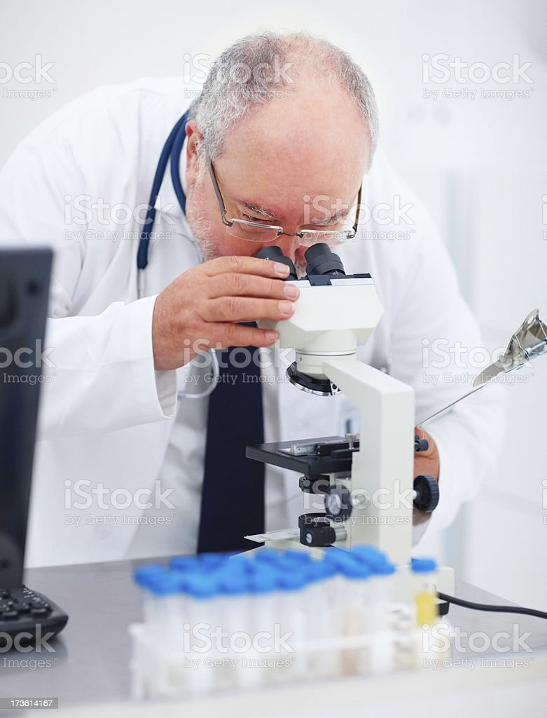 Mature doctor looking through microscope royalty-free stock photo