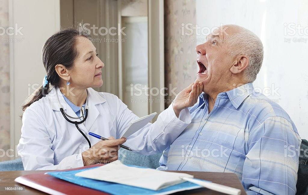 mature doctor looks the mouth of  patient stock photo