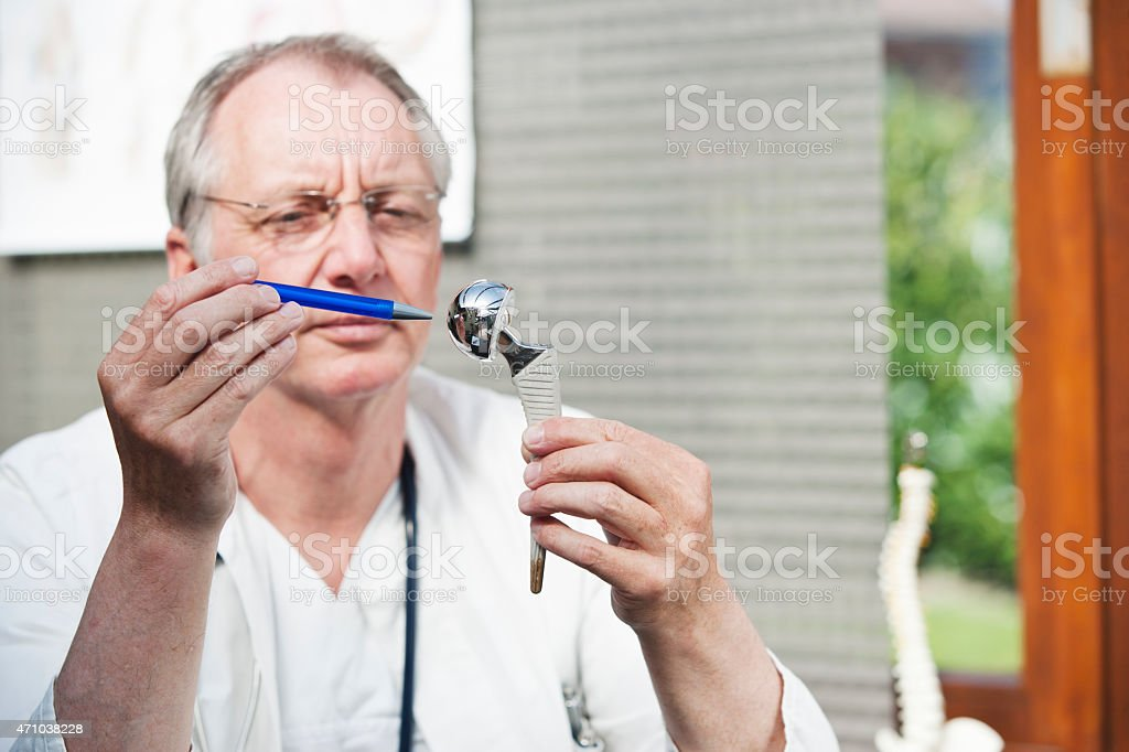Mature doctor presenting duohead hip prothesis stock photo
