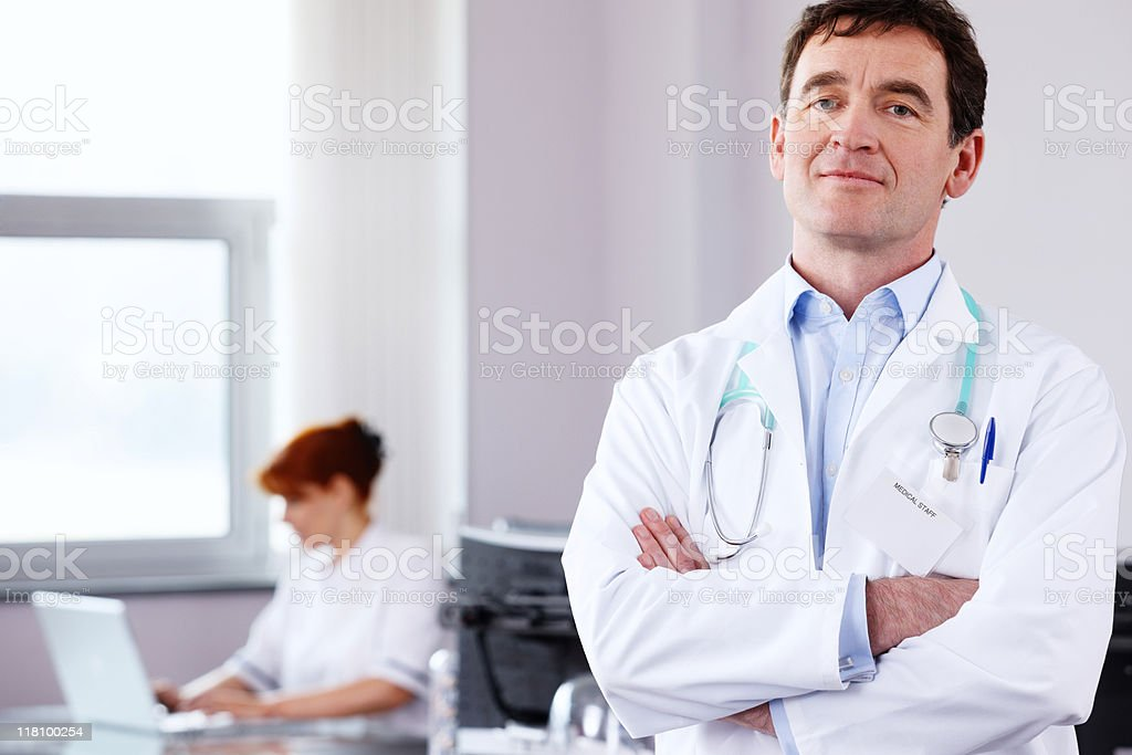 Mature Doctor standing with arms folded in modern office royalty-free stock photo