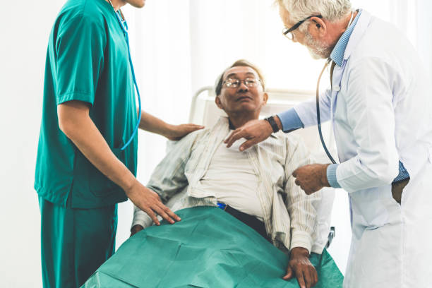 mature doctor talking and examining health of senior patient in hospital ward. medical healthcare and doctor staff service concept. - inpatient stock pictures, royalty-free photos & images