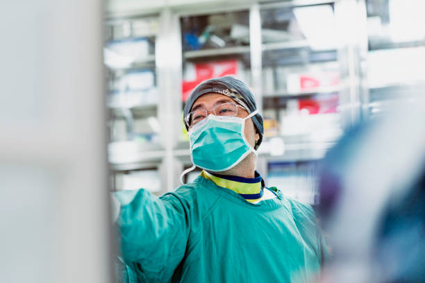 Mature doctor wearing operating gown in hospital stock photo