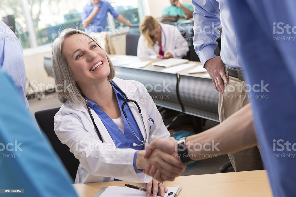 Mature doctor welcoming medical student to college seminar classroom royalty-free stock photo