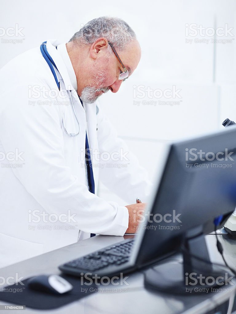 Mature doctor writing reports in hospital royalty-free stock photo