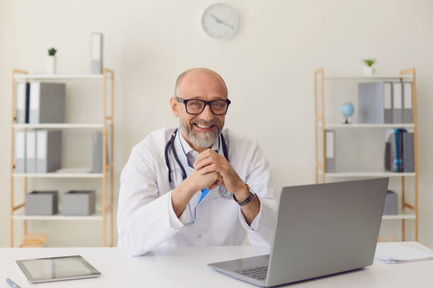 Mature doctor.A middle-aged confident doctor smiles while sitting at a table with a laptop at the workplace in the clinic office. stock photo