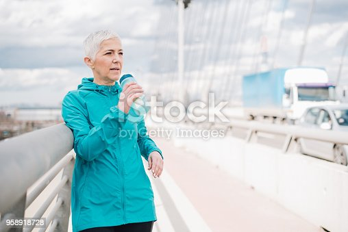 1057638814 istock photo Mature drinking water after exercise 958918728