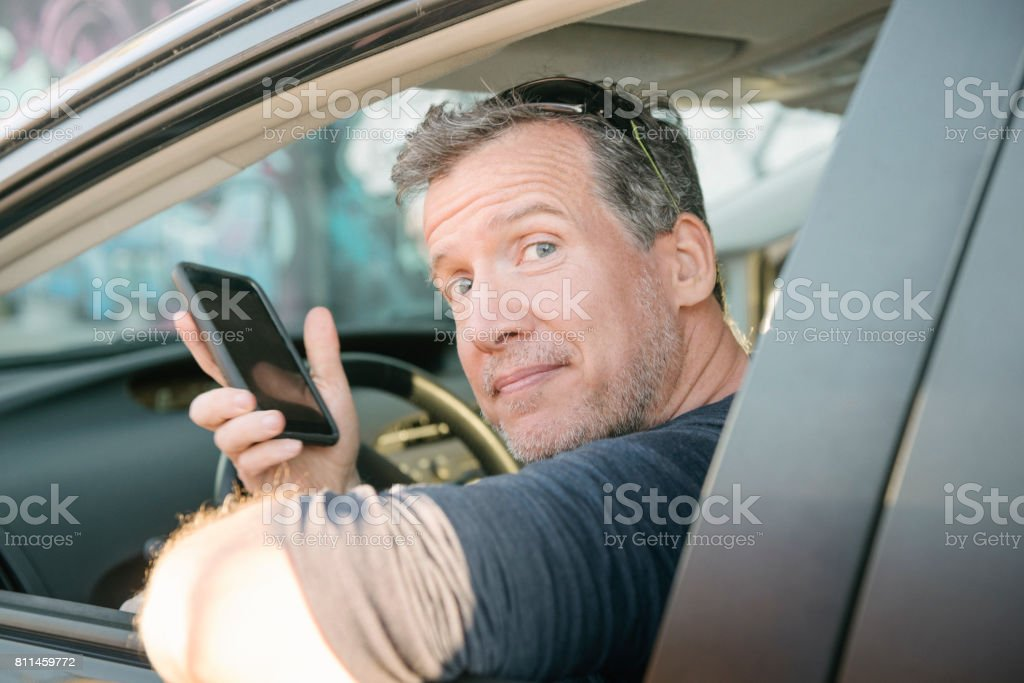 Mature Driver Waiting for Passenger with Mobile Phone Miami USA stock photo