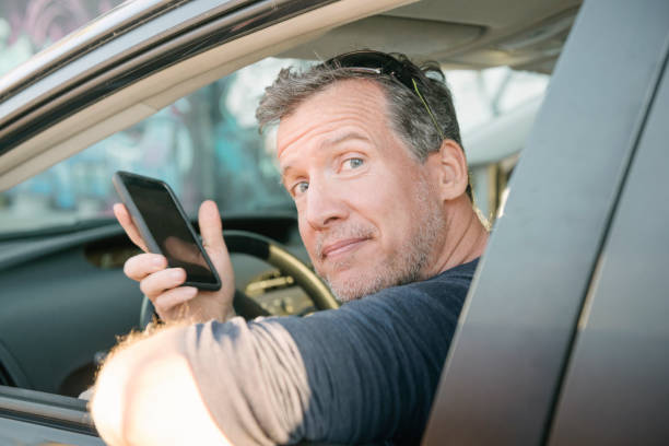 mature driver waiting for passenger with mobile phone miami usa - rideshare stock photos and pictures
