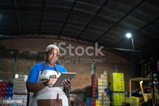 Mature employee using digital tablet at warehouse