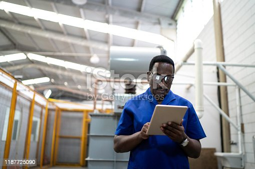 946236006 istock photo Mature employee using digital tablet in industry 1187725090