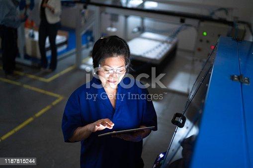 946236006 istock photo Mature employee working and using machinery in industry 1187815244