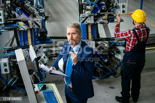 Mature engineer. Quality inspector. Mature male engineer in production stock photo. Shadow DOF. Developed from RAW; retouched with special care and attention; Small amount of grain added for best final impression. 16 bit Adobe RGB color profile.