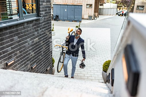 Mature Bearded businessman climbing up stairs with his bicycle on his way to work, with copy space.