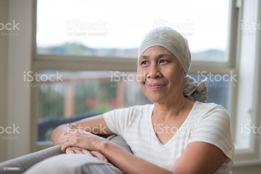 Mujer madura étnicos con cáncer usando headwrap en sofá - foto de stock