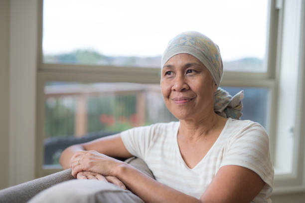 Mature ethnic woman with cancer wearing headwrap on couch stock photo