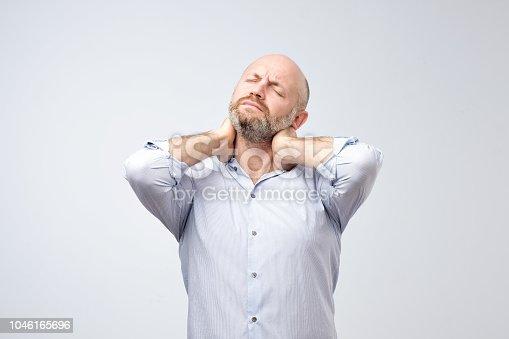 istock Mature european man with beard with neck pain 1046165696