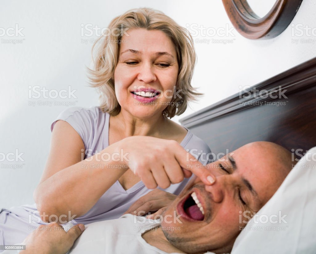 Mature exhausted  girl looking at snoring boyfriend stock photo