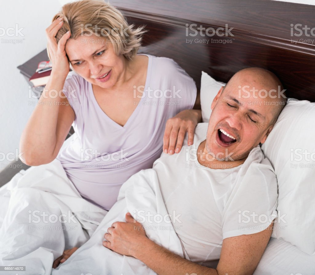 Mature exhausted woman disturbed with partner snores stock photo