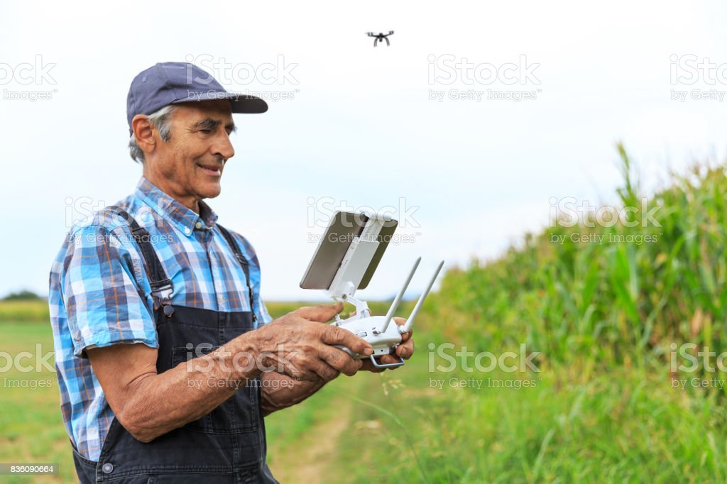 Mature farmer flying a drone over a field stock photo