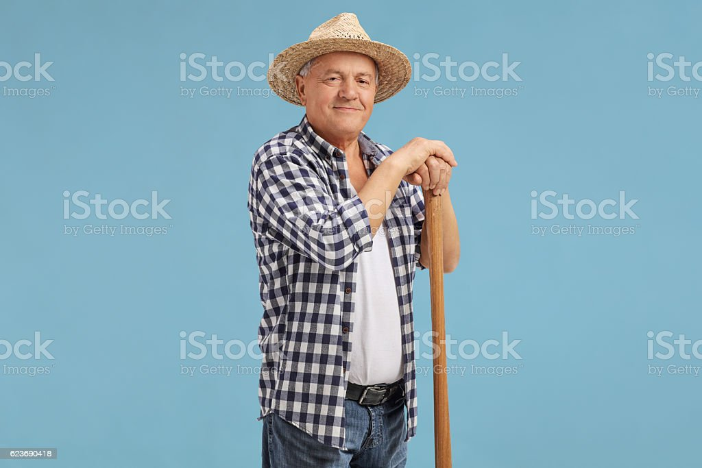 Mature farmer posing on blue background stock photo