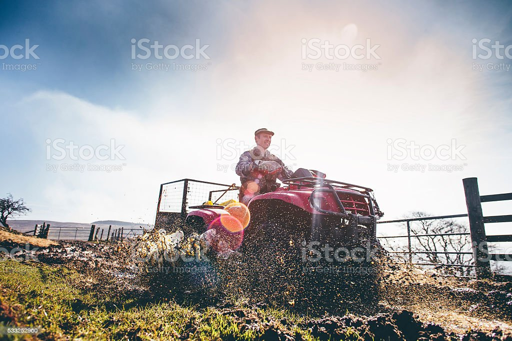 Mature Farmer Riding a Quad Bike stock photo