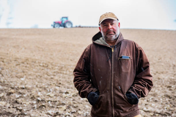 A mature farmer standing in a field with sleet falling stock photo