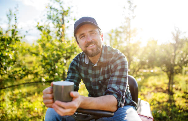 a mature farmer with cup of coffee outdoors in orchard, resting. - coffee farmer foto e immagini stock