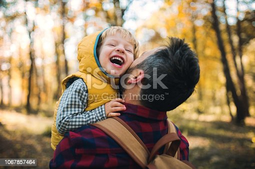 istock A mature father holding a toddler son in an autumn forest, having fun. 1067857464