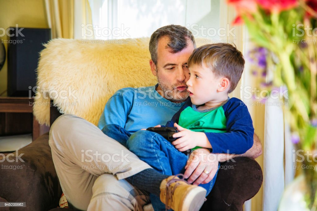 Mature father whispering hints for video game to his young son stock photo