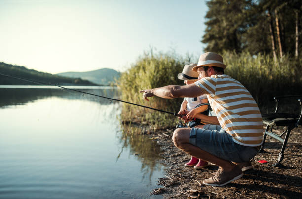 A mature father with a small toddler son outdoors fishing by a lake. A mature father with a small toddler son outdoors fishing by a river or a lake. fishing stock pictures, royalty-free photos & images