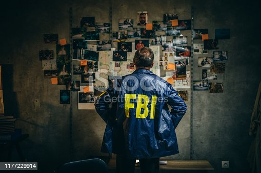 One man, mature FBI agent working on a case in dark office.