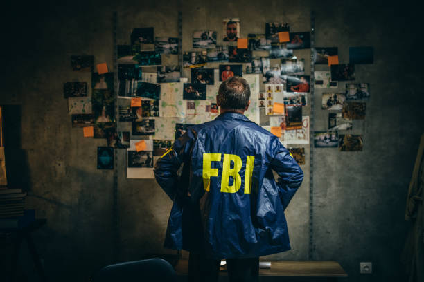 Mature FBI agent works on a case alone One man, mature FBI agent working on a case in dark office. detective stock pictures, royalty-free photos & images