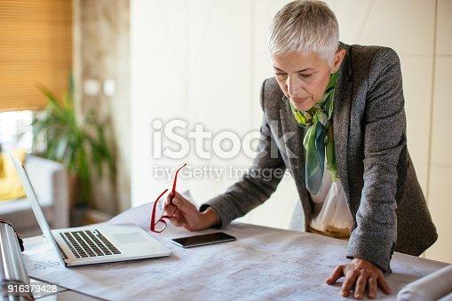 istock Mature female architect working on blueprint 916379428