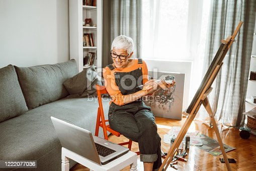 Senior female artisan painting at home during isolation have online course