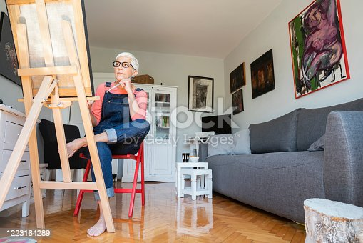Senior female artisan painting at home during isolation