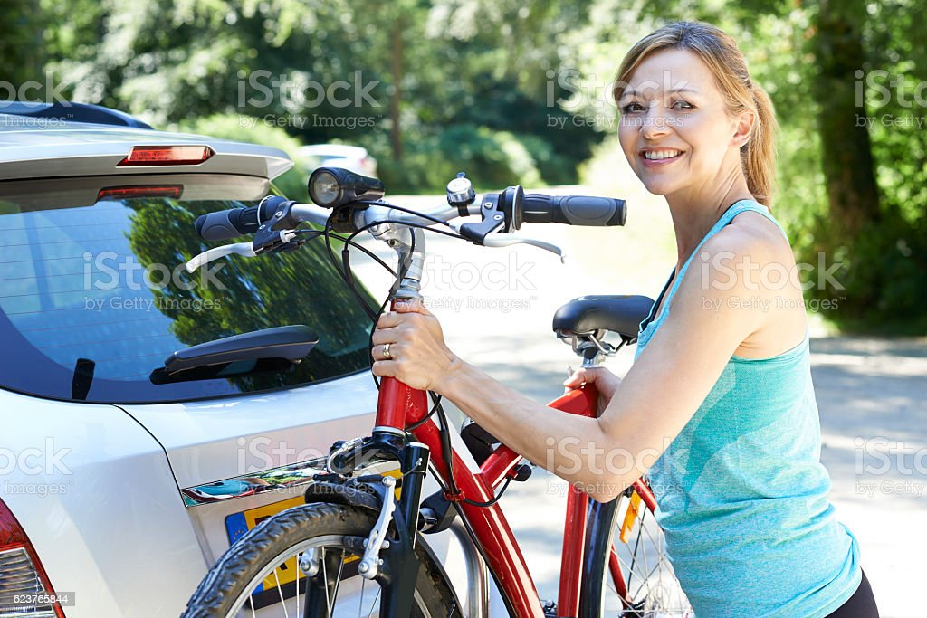 Mature Female Cyclist Taking Mountain Bike From Rack On Car stock photo