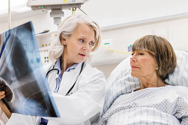 mature female doctor checking x-ray with mature patient - medical x ray stock pictures, royalty-free photos & images