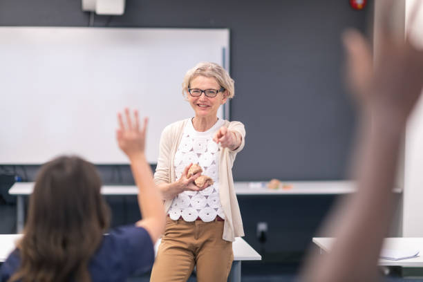 Mature female doctor demonstrates expertise in training course with medical students stock photo