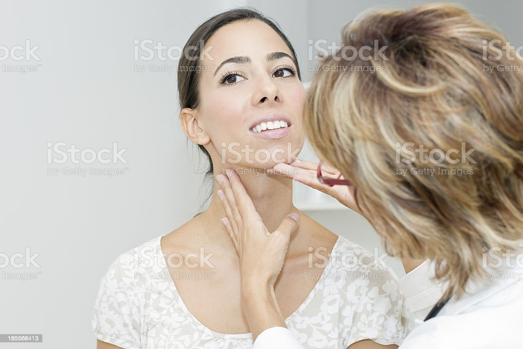 Mature female doctor examining her patient stock photo