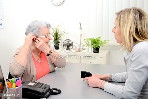 istock Mature female doctor hearing specialist in her office trying hearing aid equipment to a patient elderly senior woman 684645112