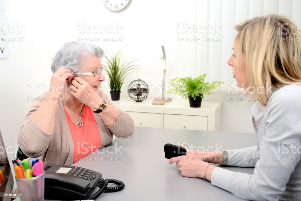 Mature female doctor hearing specialist in her office trying hearing aid equipment to a patient elderly senior woman stock photo