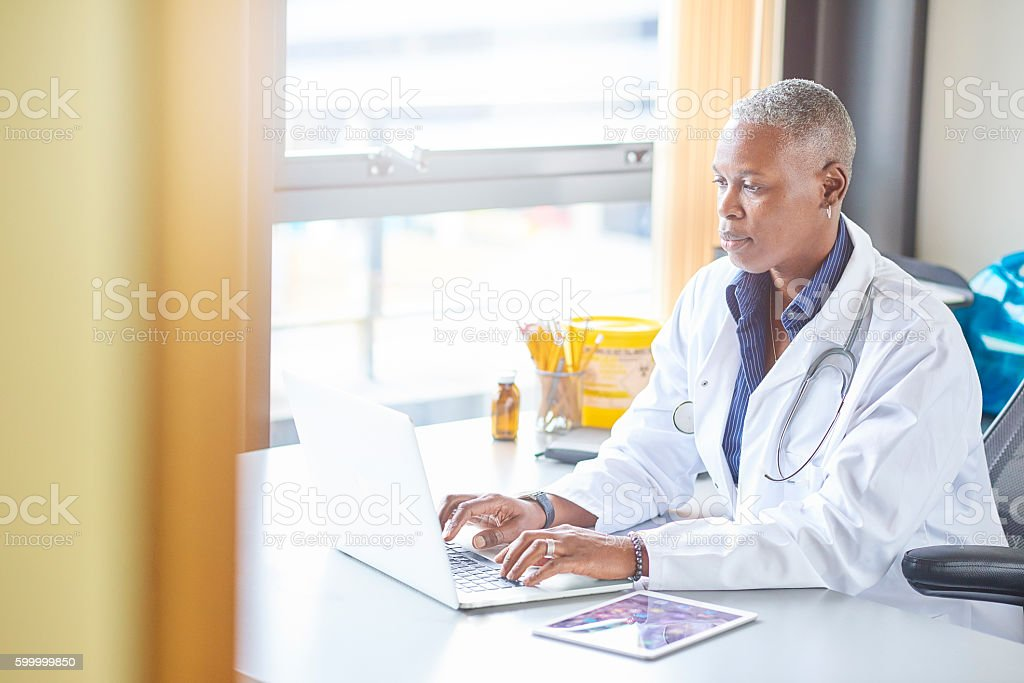 mature female doctor in her office stock photo